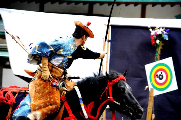 Man firing arrow from a horse in a display of yabusame, the traditional form of Japanese horseback archery