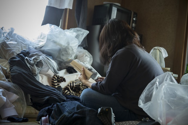 Woman sitting in filthy room