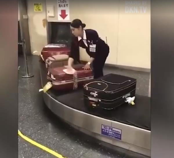 Woman in Japan wiping down bags from plane.
